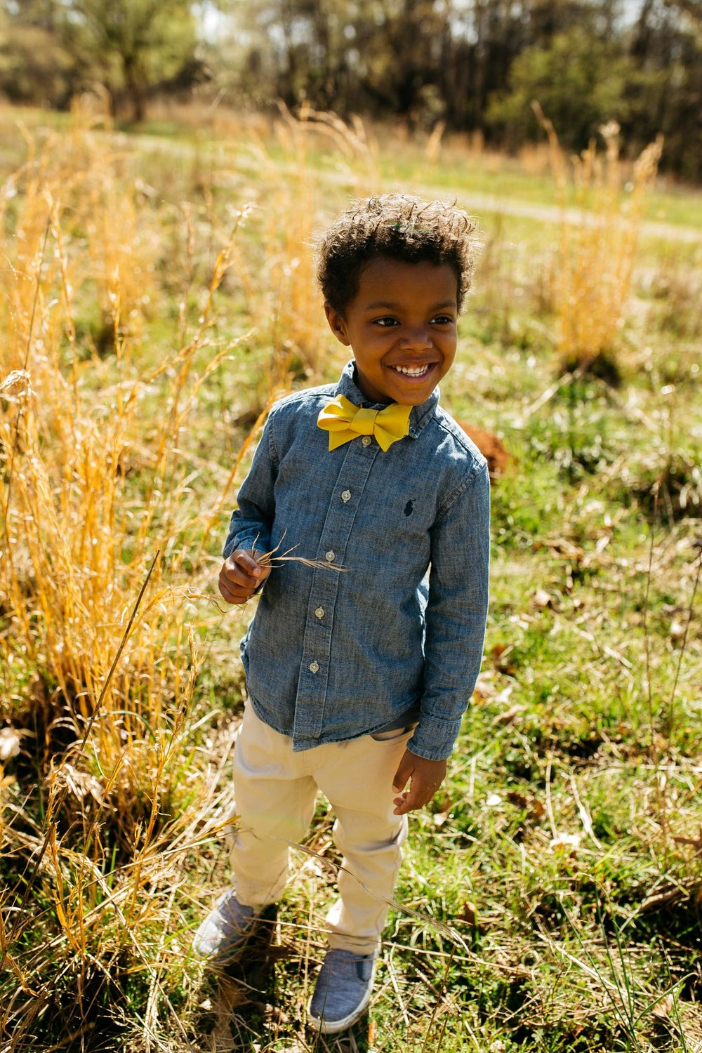 Little boy wearing matching mustard yellow bow tie and chambray shirt outfit for Mommy + Me photo session in Sweetwater Creek State Park, Lithia Springs, Georgia