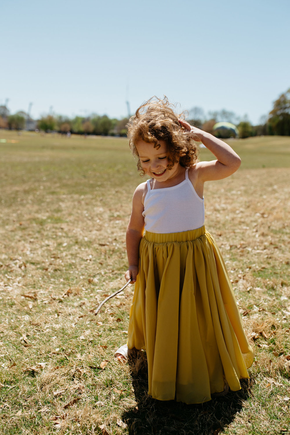 Little girl wearing matching mustard yellow maxi skirt outfits for Mommy + Me photo session in Grant Park, Atlanta Georgia