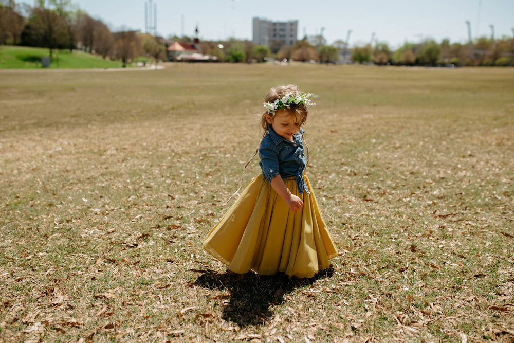 Little girl wearing matching mustard yellow maxi skirt and flower crown outfits for Mommy + Me photo session in Grant Park, Atlanta Georgia