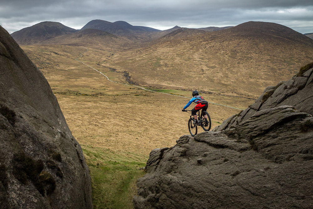 Image was taken on the south face of Hen Mountain, set firmly in the Mourne Mountains. After a long hike up from the mountain path below, my aim in the photo was to capture the extreme sport of Mountain biking. I was also keen to portray the look of the rider riding off the side of the cliff and down to the road beneath.