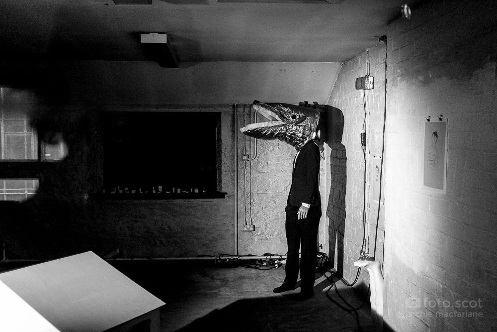 man with fish head in room- hidden door festival