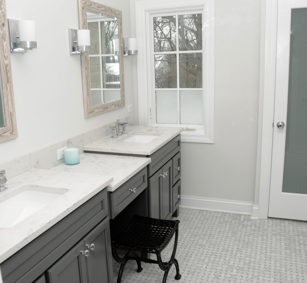 We added storage with a double vanity and desk and enclosed the toilet in its own room behind a frosted glass door for privacy.