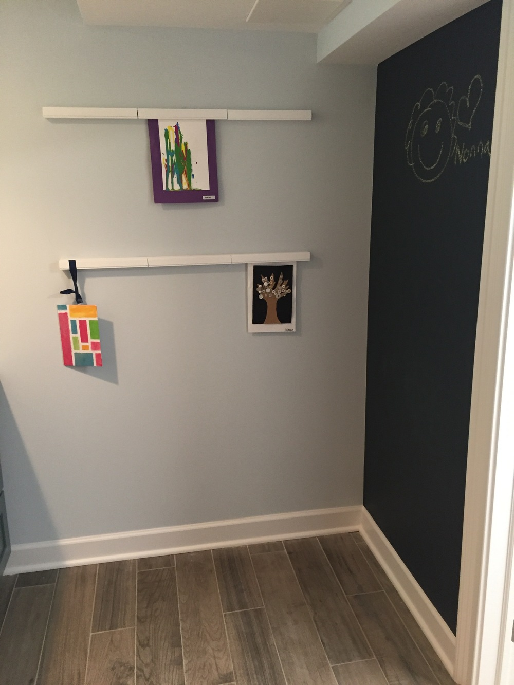 Wall-mounted racks have magnetic locks to hang dry art projects. A chalk-board wall completes the 42 square foot space.