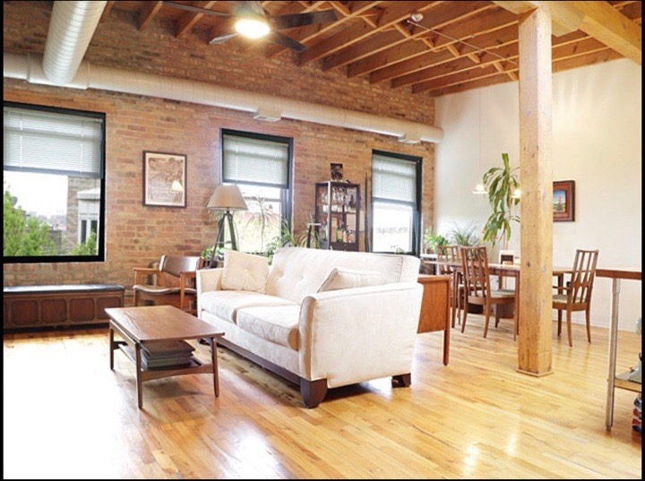 The combined family/dining room. Exposed brick with over-sized windows and large wood beams echo the industrial history of this building. The kitchen and family/dining room all bleed into each other in one large and undefined space during the pre-construction phase.