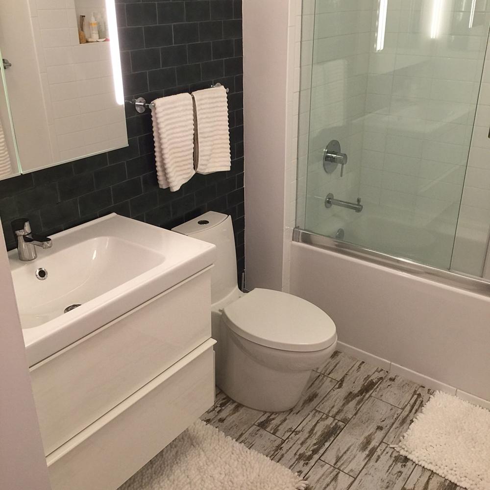 A new wall-mounted vanity, tile, lighting, and plumbing fixtures modernize the bathroom