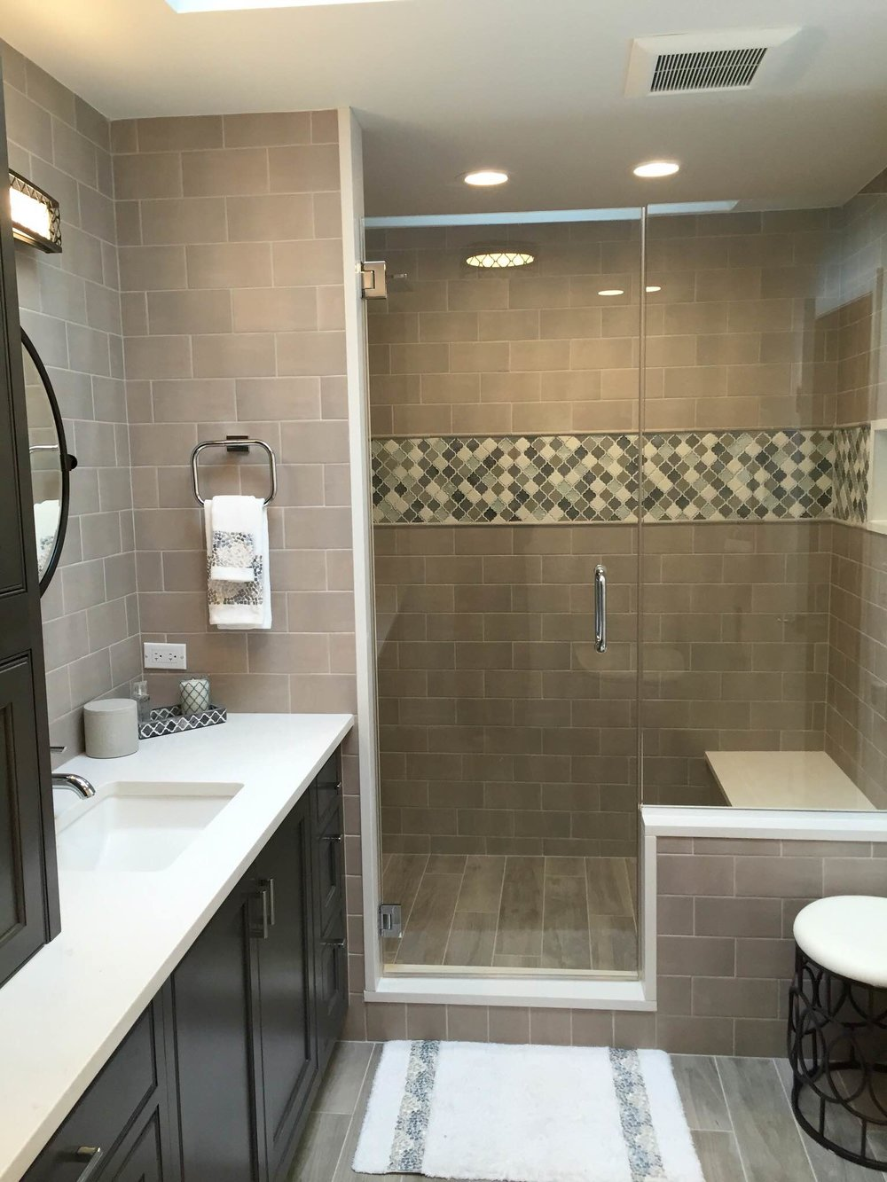 The new bathroom features a warmer color palette, heated floor, and an expanded shower with a bench.