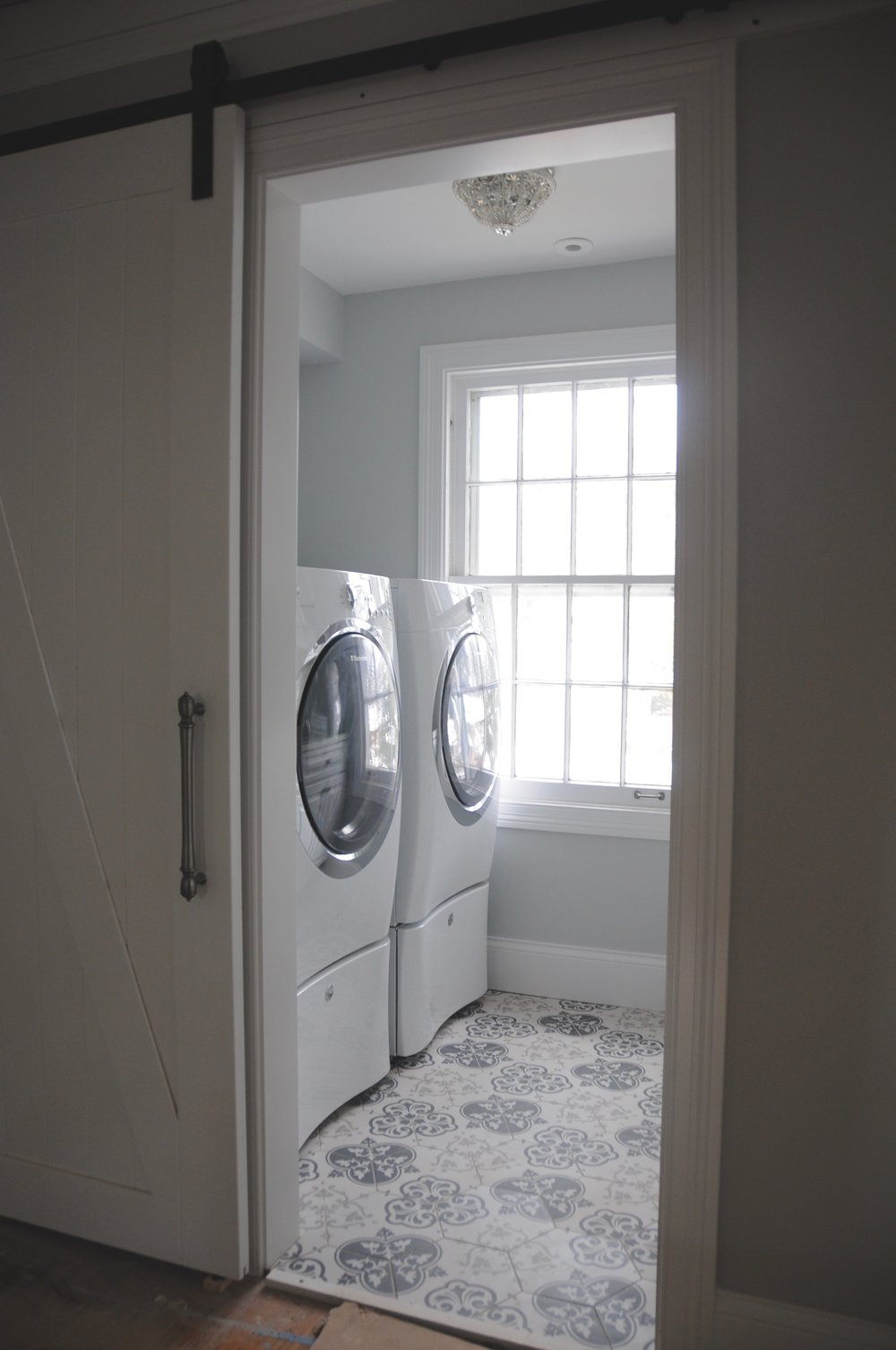 Mounting the machines on pedestals offers good ergonomics for loading and unloading the laundry as well as extra storage. A client let us repurpose the mini crystal flushmount on the ceiling when she no longer needed it. It's the perfect size and  a good use of surplus lighting fixtures. Who says your laundry room can't have a little glamour?
