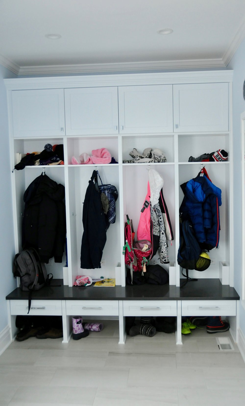 Each child has a cubby with space below for shoes, a drawer, coat hooks, and a backpack hook. The mix of open and closed storage provides easy access and flexibility for storing seasonal items. Each cubby also has an outlet with USB ports. Built-in storage boxes for tablets, phones, and laptops keep the electronic devices safe and in place while charging.
