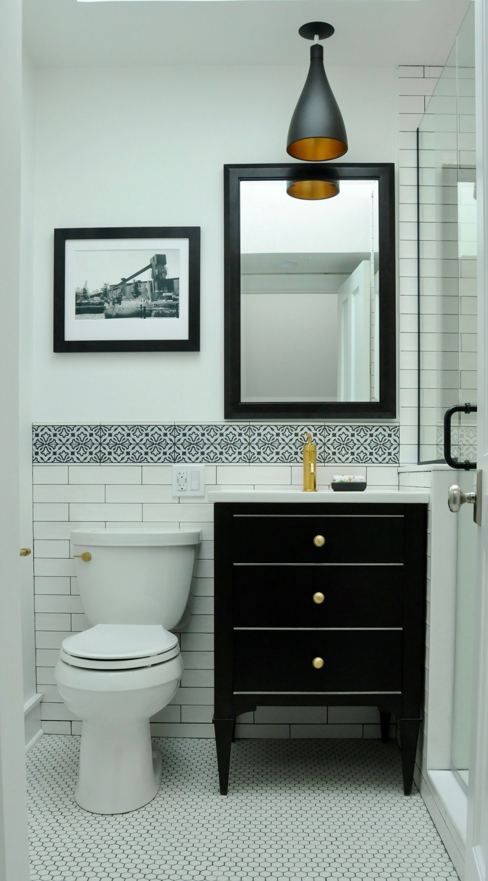 The new bathroom exchanges the short pedestal sink for a full-height black vanity with storage, the polished chrome for warmer tones, and the ongoing maintenance of white grout for charcoal.