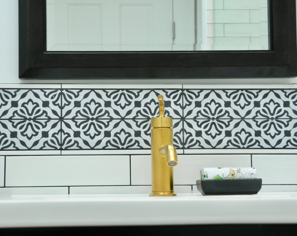 Black & white doesn't have to be old-fashioned or overtly masculine. Here we used an elongated white subway tile to update a classic look and softened the visuals with a decorative backsplash.