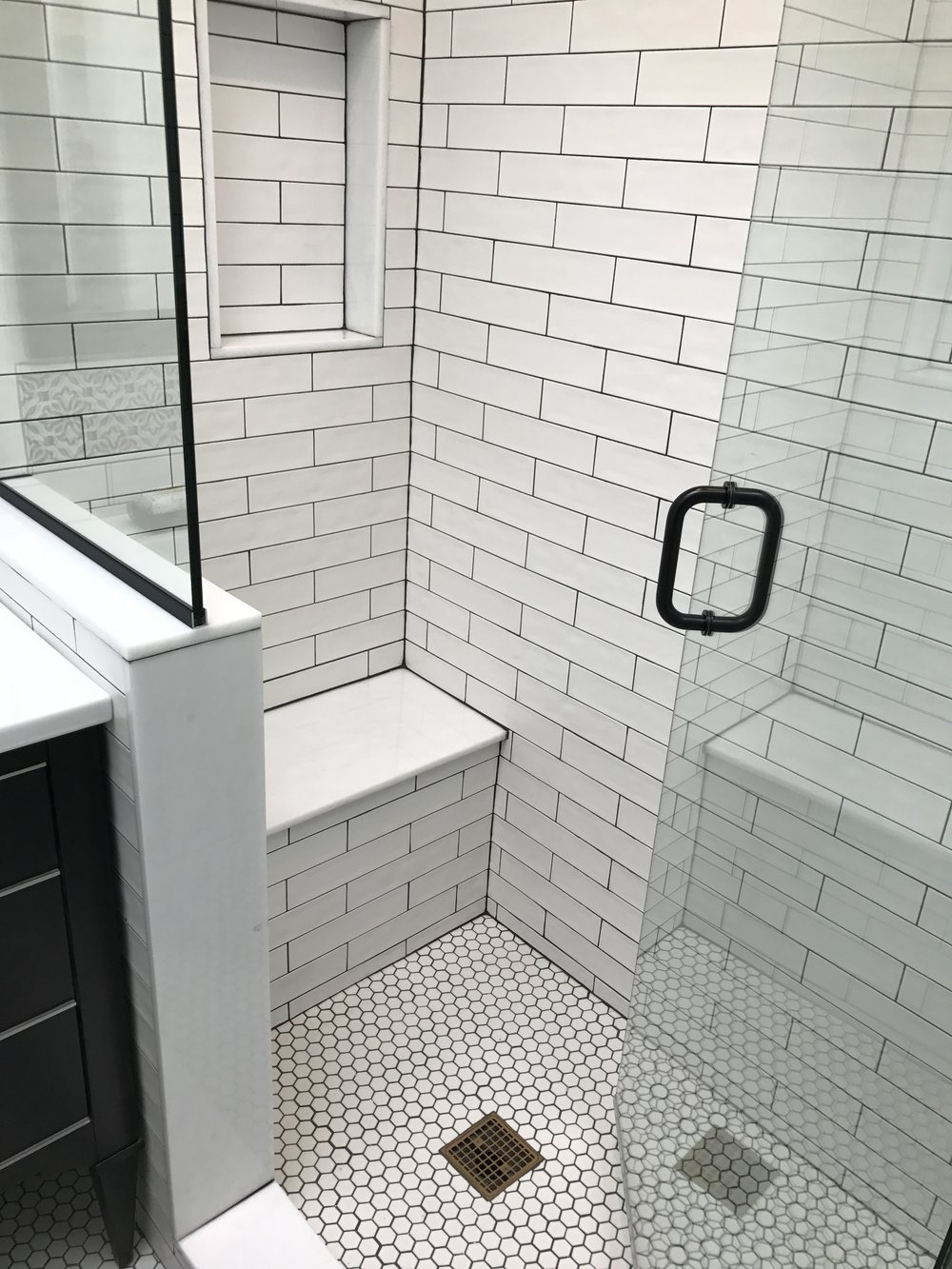 The addition of a small bench and shower niche adds comfort and storage for a more functional shower.