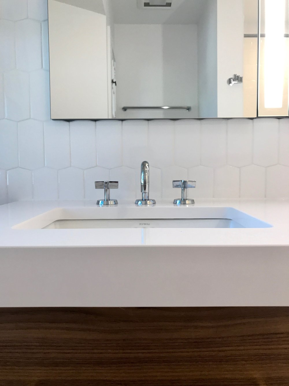 Faucets made in Brooklyn by  Watermark  and medicine cabinets from Robern. Tile from Ann Sacks. The 7 cm profile of Casesarstone white quartz complements the modern aesthetic.