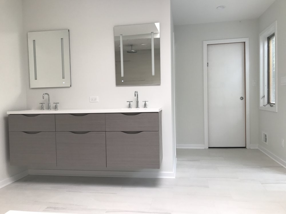 A view of the floating vanity opposite the shower, unadorned by hardware and matched to the spare simplicity of the bathroom.