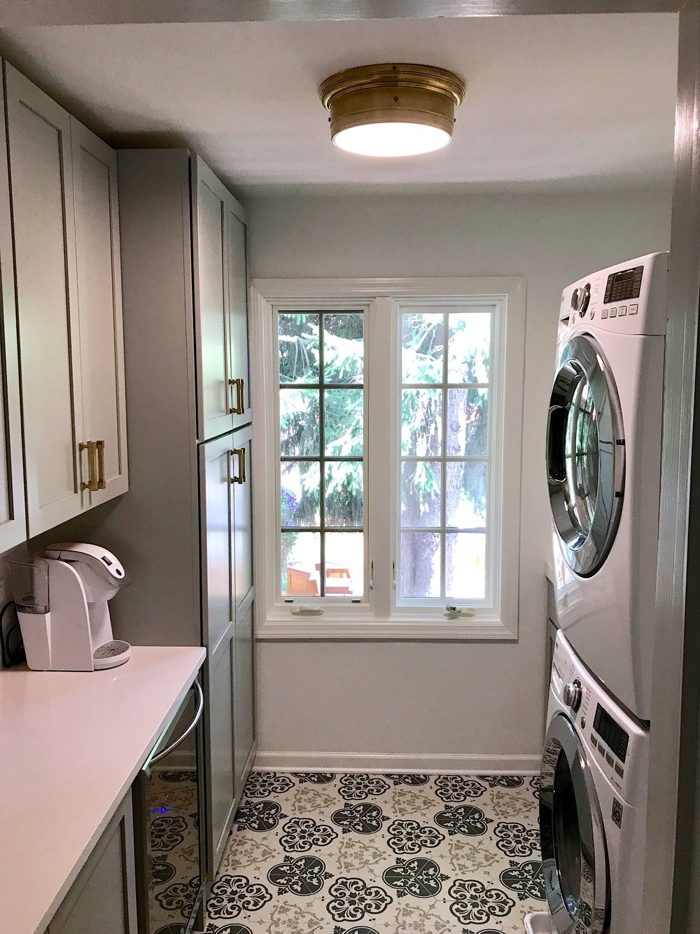 Goodbye to a single-purpose storage room, and hello to a multi-function laundry room. Cabinetry for storage on the left, with stackable full-size laundry machines and sink on the right.