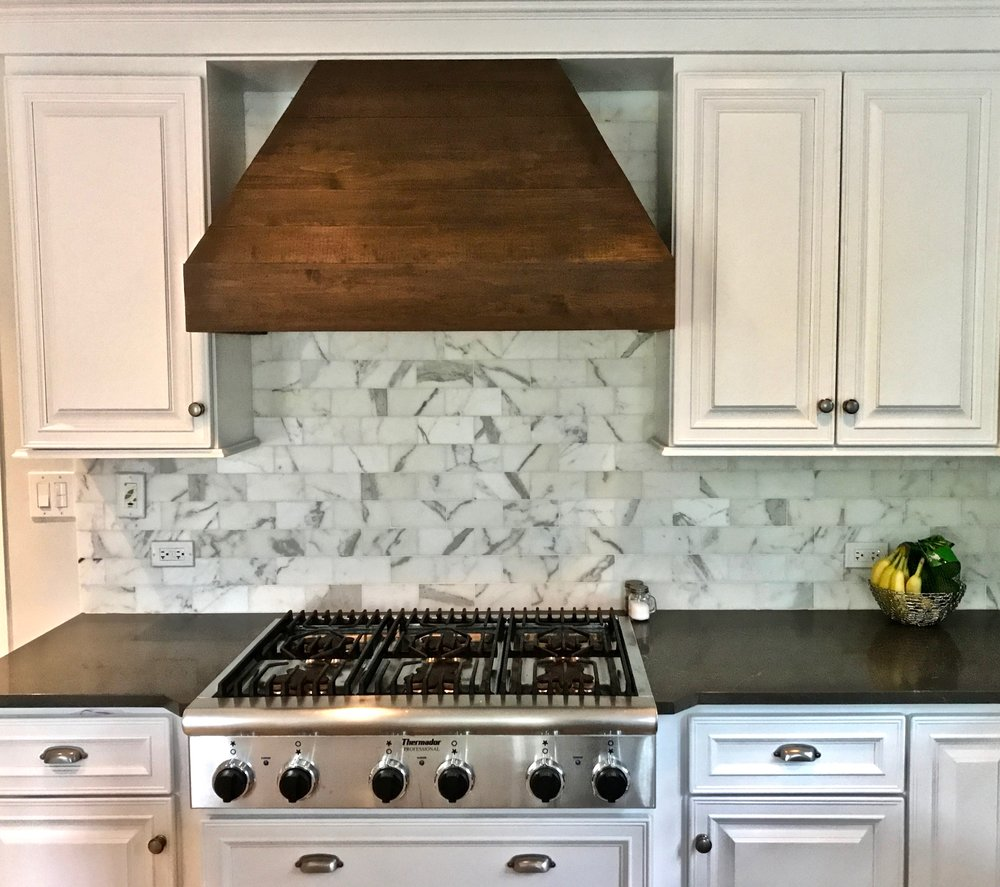 We clad the hood in wood with a custom stain to match the new shelving near the window.A view of the hood surrounded by new hardware, sink faucet, freshly painted cabinets and walls,Calacatta backsplash, and new countertops.