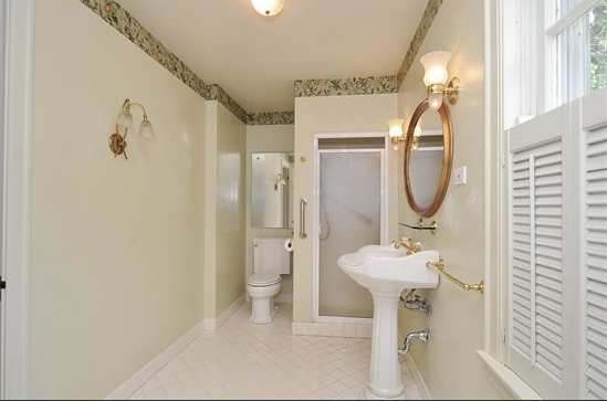 """The original master bathroom featured a 36"""" x 36"""" shower, a green wallpaper border near the ceiling, and gold accents. An orphaned pedestal sink stood guard on the 14 foot long wall."""