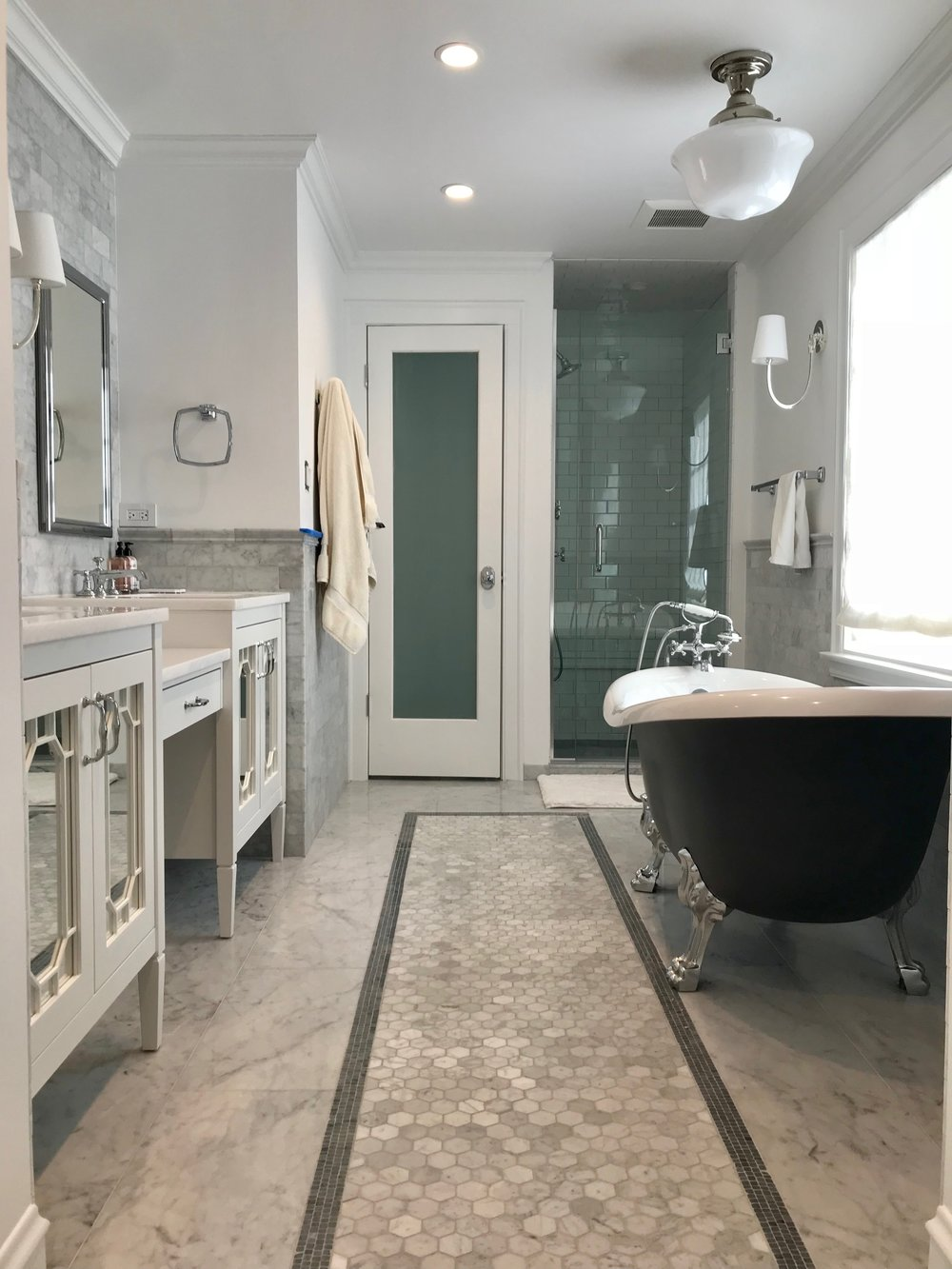 """We recessed the 84"""" vanity into the wall to accommodate the free-standing tub. We used Walker Zanger's Grigio Scuro mosaic to create a border around the white carrara hex tile along the center line of the bathroom."""