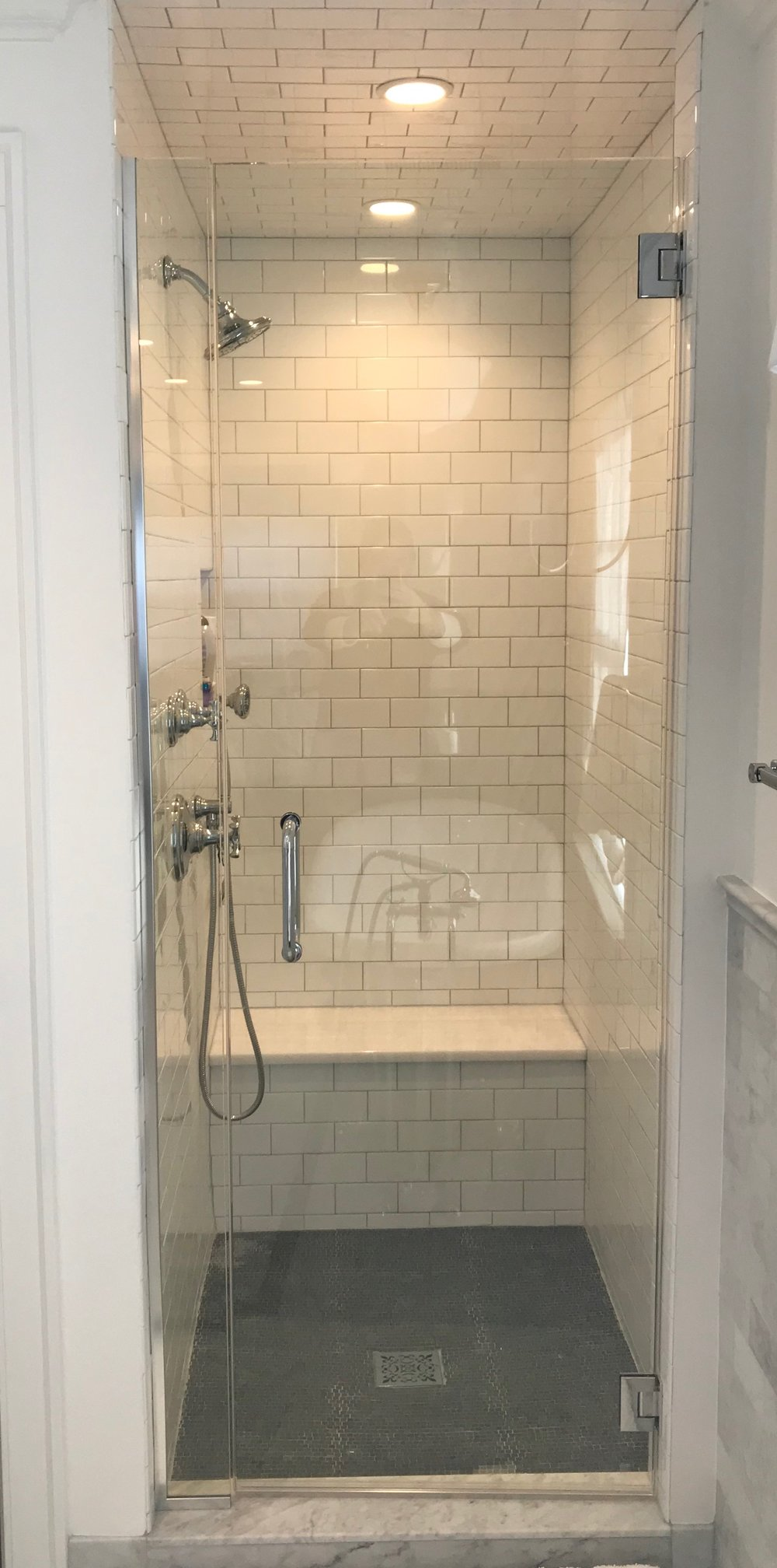Kallista Bellis shower pieces and a white quartzite bench match the vanity top and sink faucets.