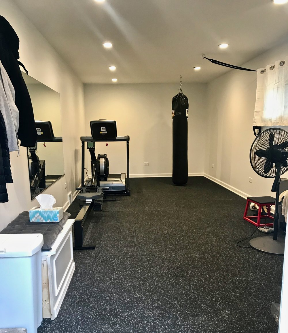 "The former garage comfortably holds a treadmill, rowing machine, heavy bag, TRX system, and more, all on a 3/4"" thick rubberized floor. No more excuses for skipping a workout when you have this attached to your home."