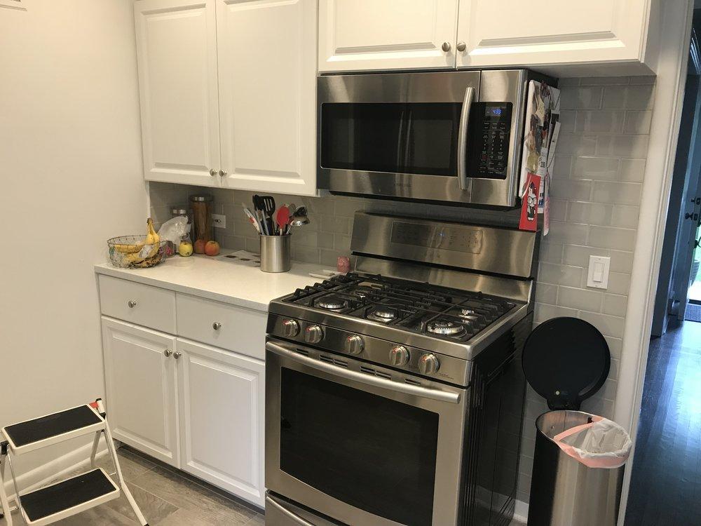 The original cooking appliances opposite the sink wall. One disadvantage of stock cabinetry is that it can lead to odd configurations if the wall dimensions are not a good fit for the stock cabinetry dimensions.
