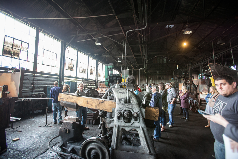 Members of the Wheeling Young Preservationists walk through the long factory with their tour guides.