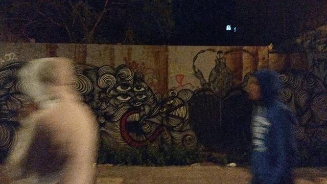 Young refugee men passing in front of street art in a area of prostitution in Athens.