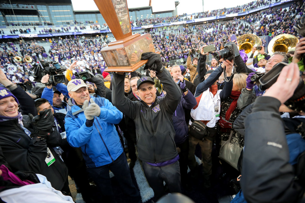 University of Washington Huskies Football Head Coach Chris Petersen Hoists Apple Cup Trophy after beating Washington State University Cougars