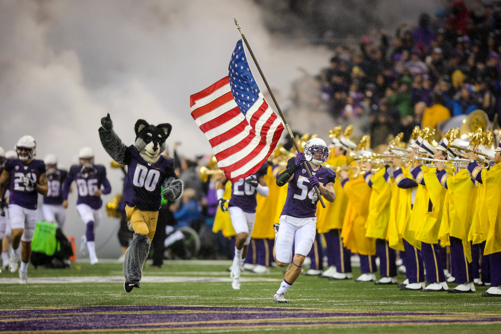 University of Washington Huskies Football Linebacker Matt Preston Hoists the American United States of America Flag on Run out Pregame