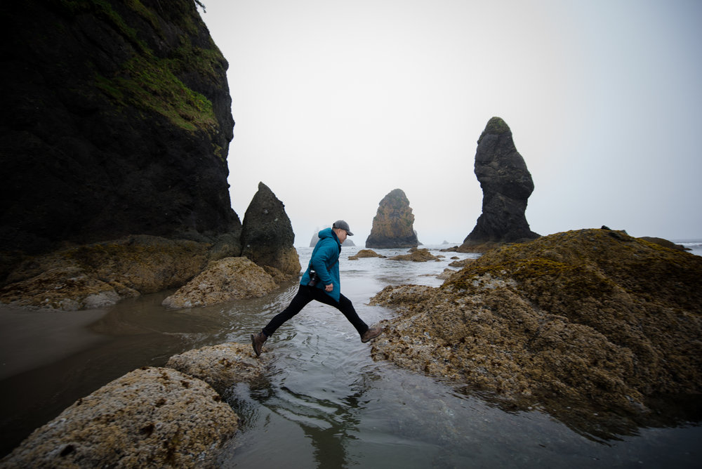 Jeffrey Le jumps between two rocks at Point of the Arches at Shi Shi Beach along the Olympic Peninsula Pacific Northwest Coast Washington