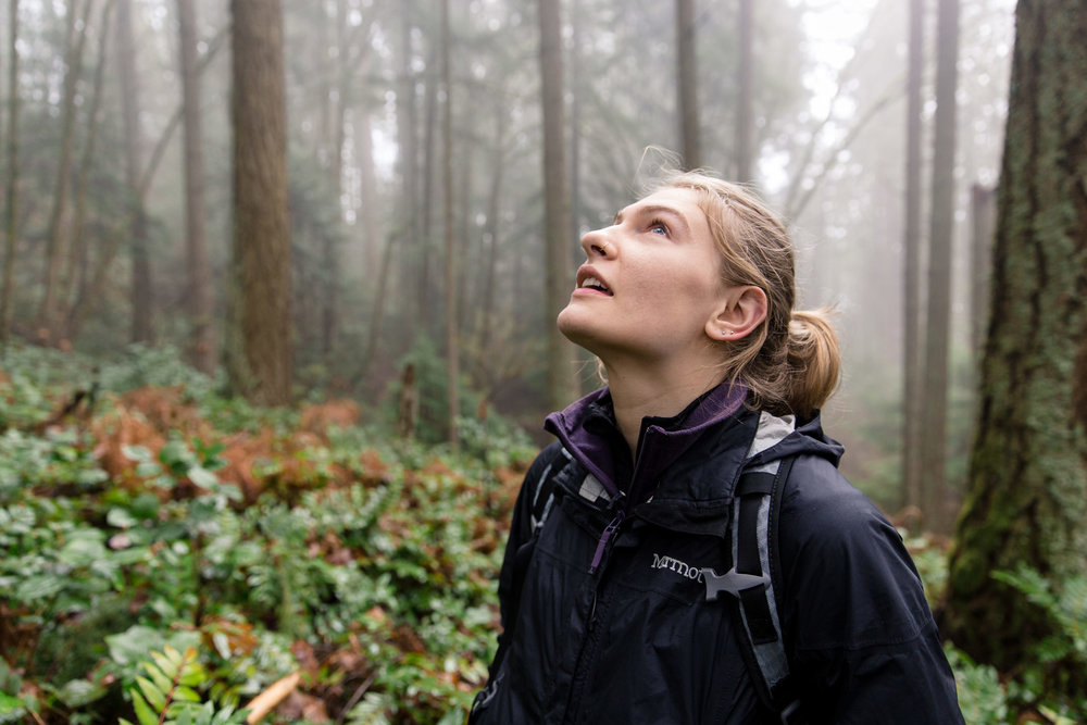 Emily Chambard gazes upwards into the woods and trees during a hike up to Poo Poo Point in the Pacific Northwest Washington