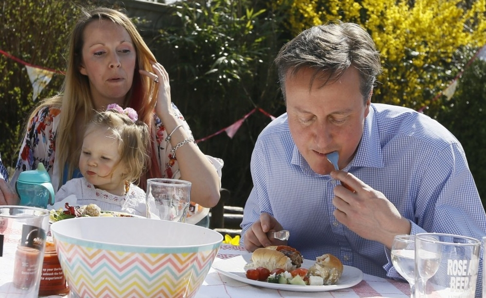 British Prime Minister David Cameron invited reporters to watch him eat a hot dog with a knife and fork further fueling a food fight for political office, which could spill over to the U.S. presidential election next year. (Photo by Kirsty Wigglesworth/AFP)