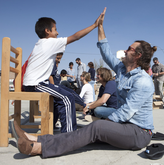 TOMS CEO Blake Mycoskie fits a Peruvian child with shoes. The company recently utilized virtual reality to help tell its story.
