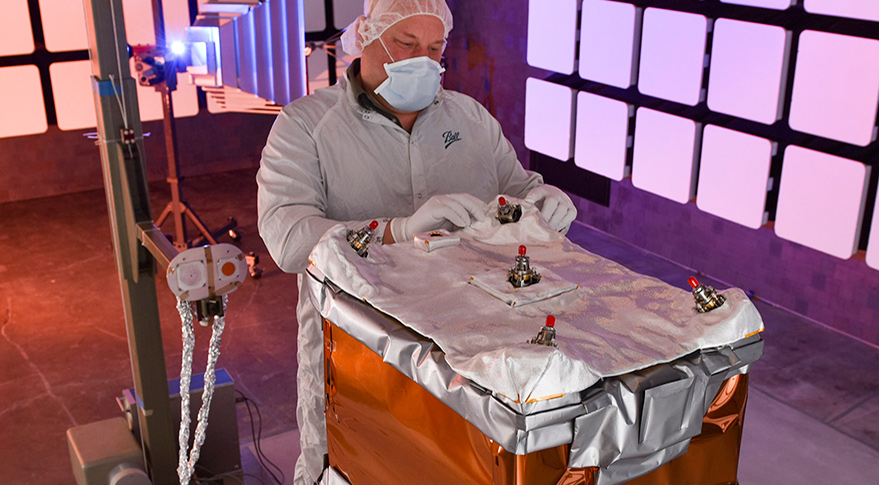 A Ball Aerospace engineer adjusts the thermal insulation on NASA's Green Propellant Infusion Mission spacecraft bus following integration of the propulsion system. Credit: Ball Aerospace