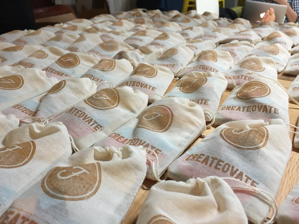 A collection of hand-stamped Createovate pouches being prepared for KIDfest