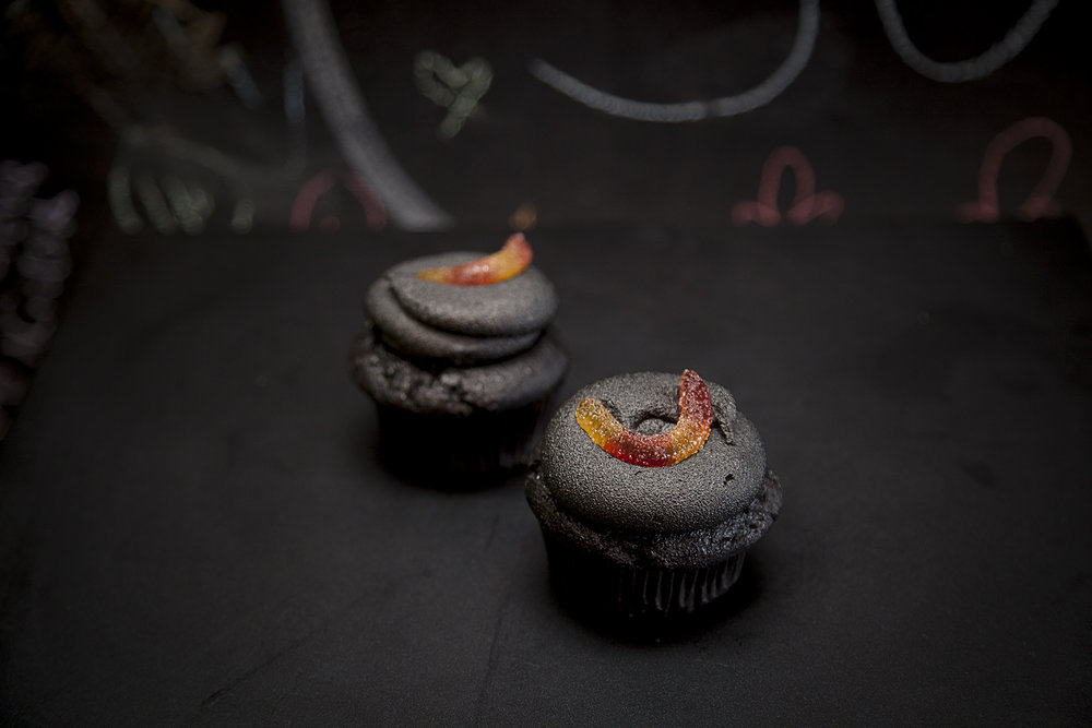 MIDNIGHT - $4.5 - Black chocolate cupcake filled with orange flavour & coloured coconut whip cream. Topped with black chocolate buttercream frosting and a creepy crawly sour gummy worm.