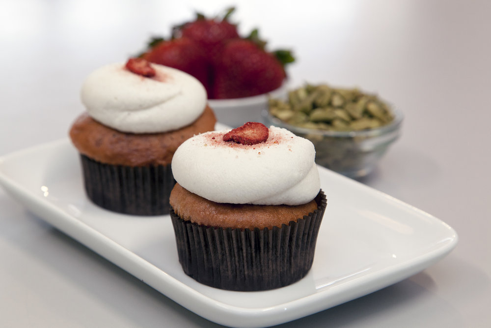 Strawberry CardaMOM Cupcake -  Strawberry cake, center filled with fresh roasted strawberries and ground cardamom coconut whip cream. Topped with vanilla and cardamom buttercream frosting.