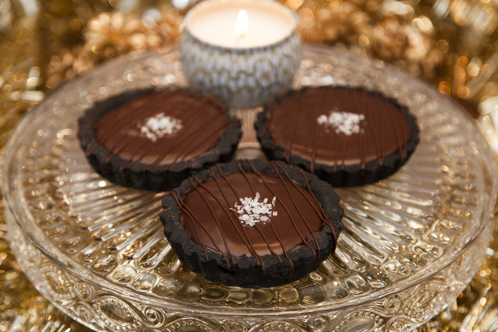 "4"" Salted Chocolate Ganache Bourbon Caramel Tart  - The perfectly personal tart for you or a group. Tender black chocolate pastry filled with a thick layer of bourbon caramel and topped with a deliciously dark chocolate ganache. Sprinkled with Maldon sea salt flakes."