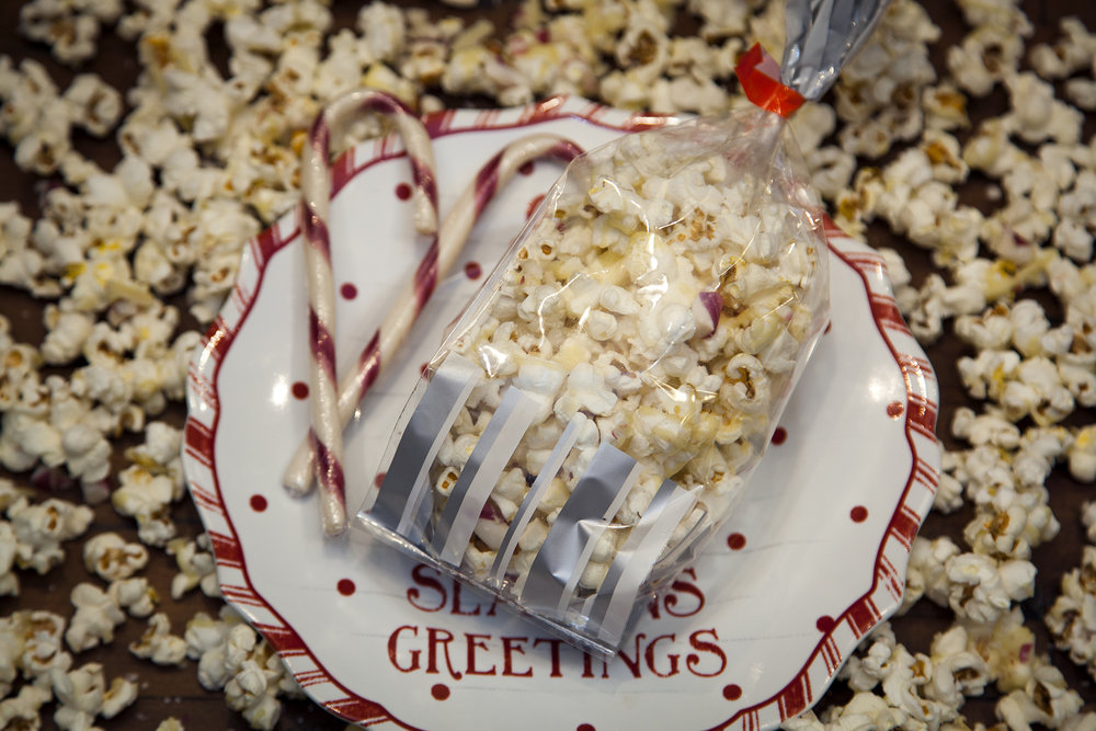 Peppermint White Chocolate Popcorn w/ Crushed Candy Cane  - Stuff those stockings with the kind of nourishment needed to get you through the long haul of opening all those gifts on Xmas Day! Popcorn drizzled with peppermint white chocolate and sprinkled with crushed candy canes. It's what elves eat!
