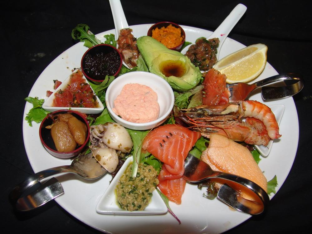 ASSIETTE DE TAPAS SAVEUR DU MONDE    Tartare de thon et saumon, avocat, tapenade, crevette de Madagascar, brochettes,saumon fumémaison