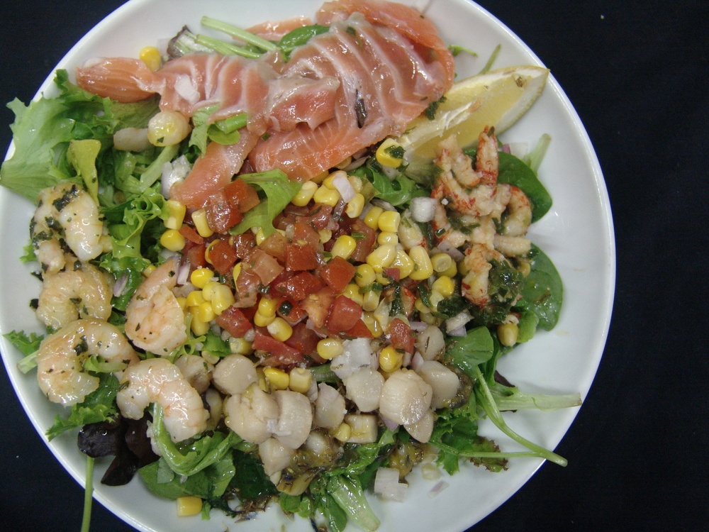 SALADE ESTIVALES DE POISSONS MARINÉES/ FUME sur un lit de salade, tomates fraîches, maïs…