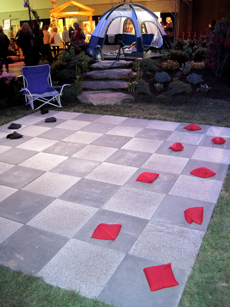 "An outdoor checkerboard leads to an elevated ""campsite"" complete with telescope for stargazing."
