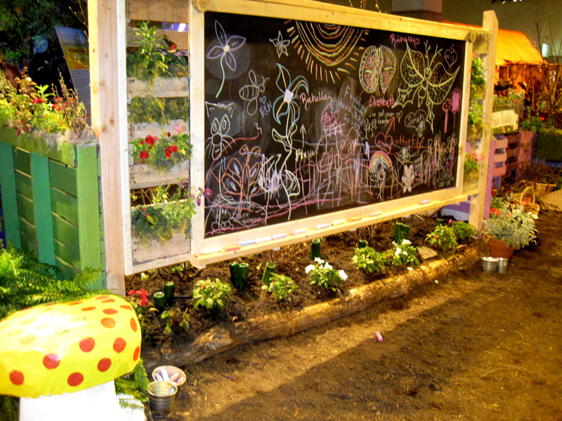 A chalkboard is surrounded by vertical gardens made of palettes.