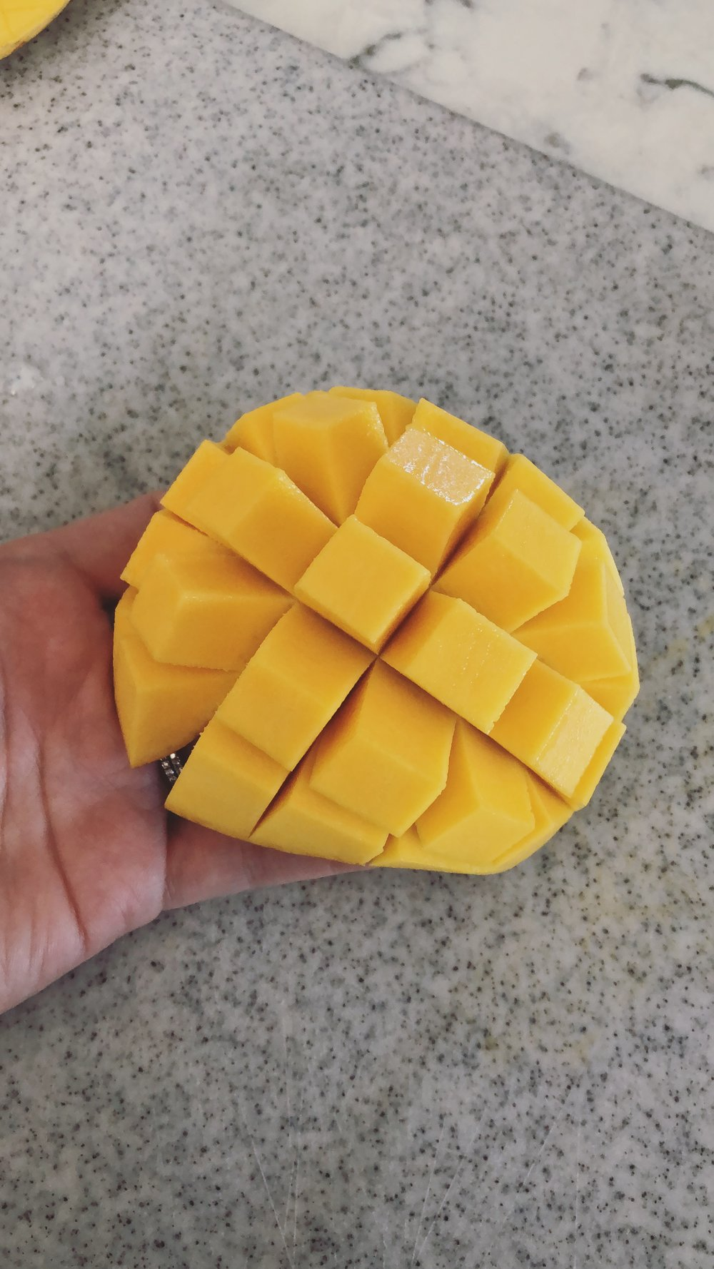 Pop it backwards and pull of the mango or carefully slice off with a paring knife.