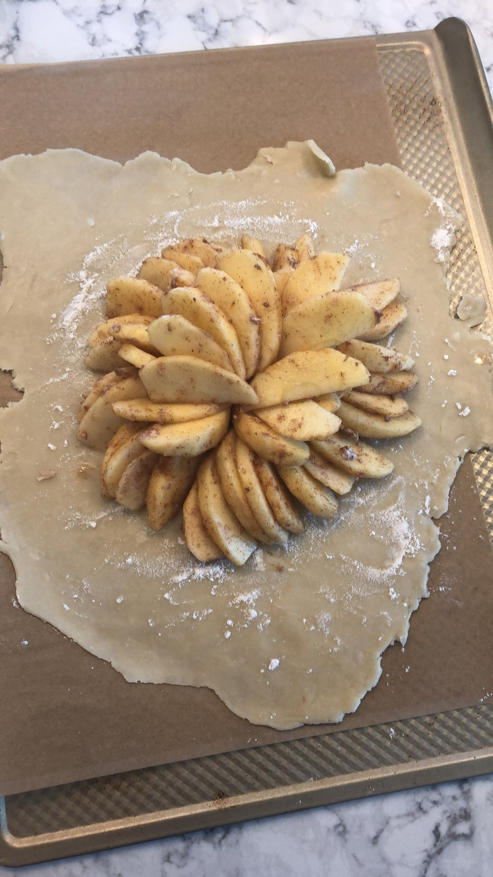 After the apples have been tossed in the sugar, cinnamon and butter, place them in a pretty pattern on the dough. Fold up the edges over the apples, brush the egg wash on the dough and sprinkle with additional cinnamon and sugar.