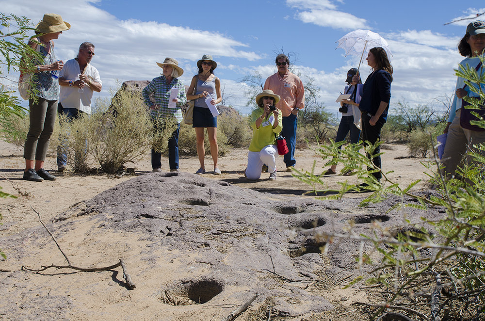 Tourists study ancient mortar holes used by the Hohokam civilization to grind mesquite beans during 500-1450 A.D.