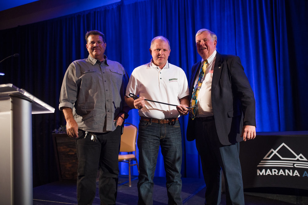 Greg Brchan and Chris Fisher accept the Branding Iron Award from Mayor Honea on behalf of Northwest Landscaping on the 2018 State of the Town stage.