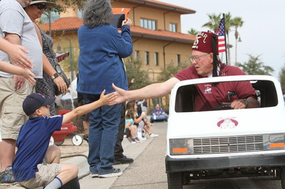 A Shriner gives a high five during the Marana Founders' Day Parade.