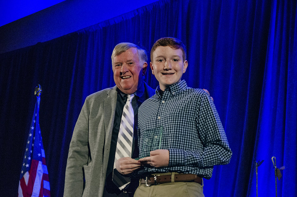 Jacob Cox accepts the Youth Legacy Award from Mayor Honea on the 2019 State of the Town stage.