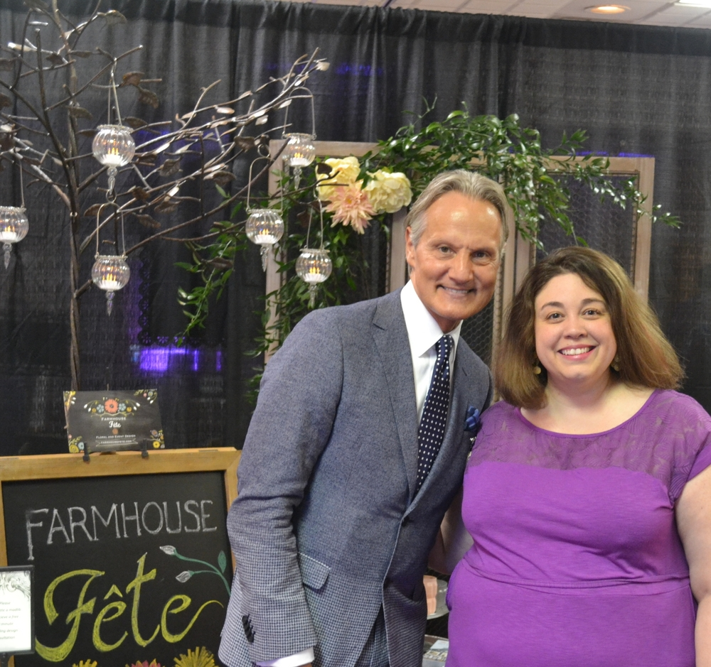 Farmhouse Fête Event Planning Advisor Cassandra Poling poses with Monte in front of the Farmhouse Fête booth.