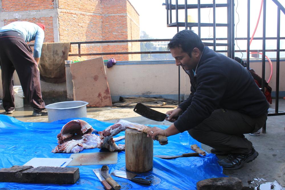 Pastor Dinesh butchering the goat for our Christmas dinner